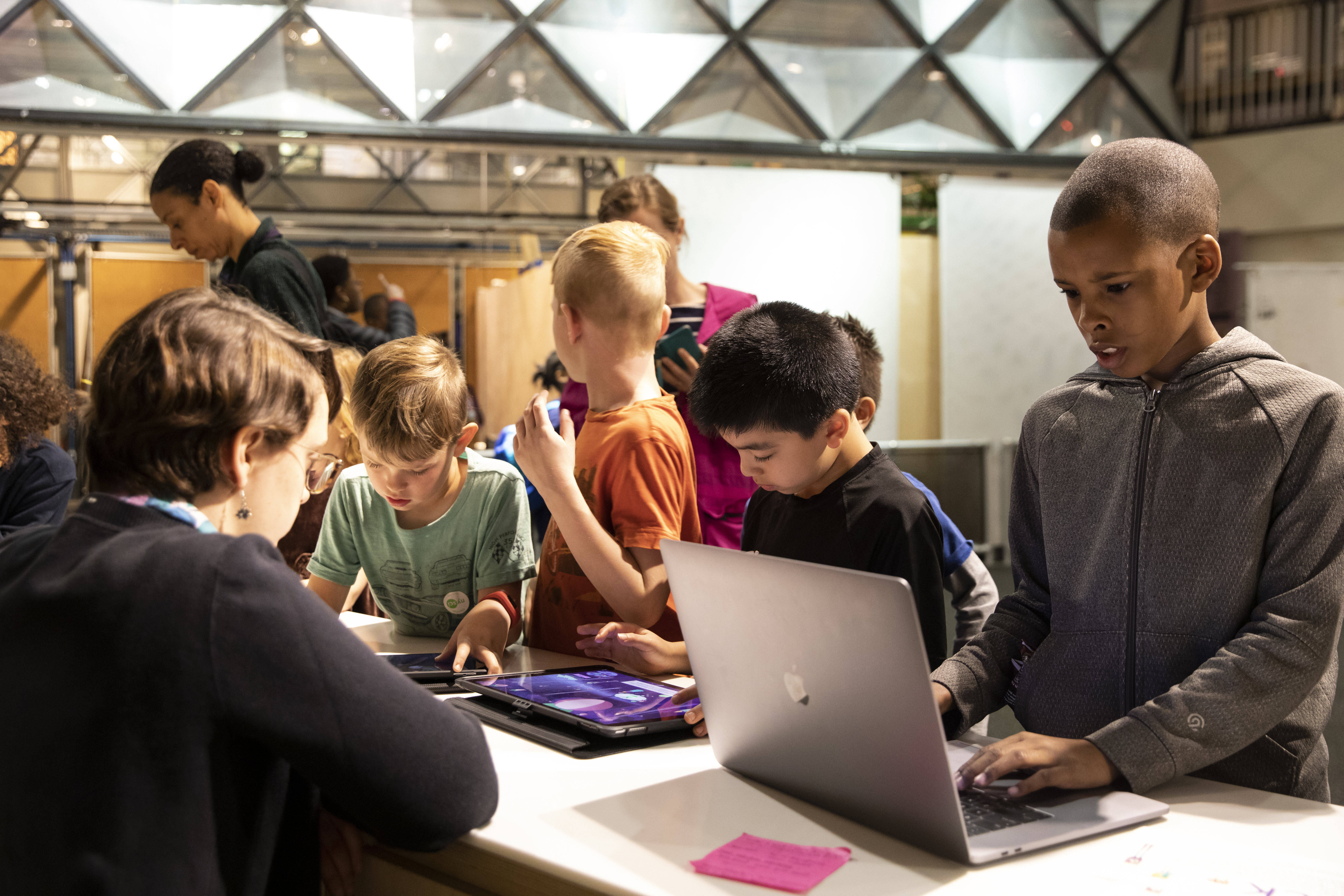 Children on computers in a museum or maker space
