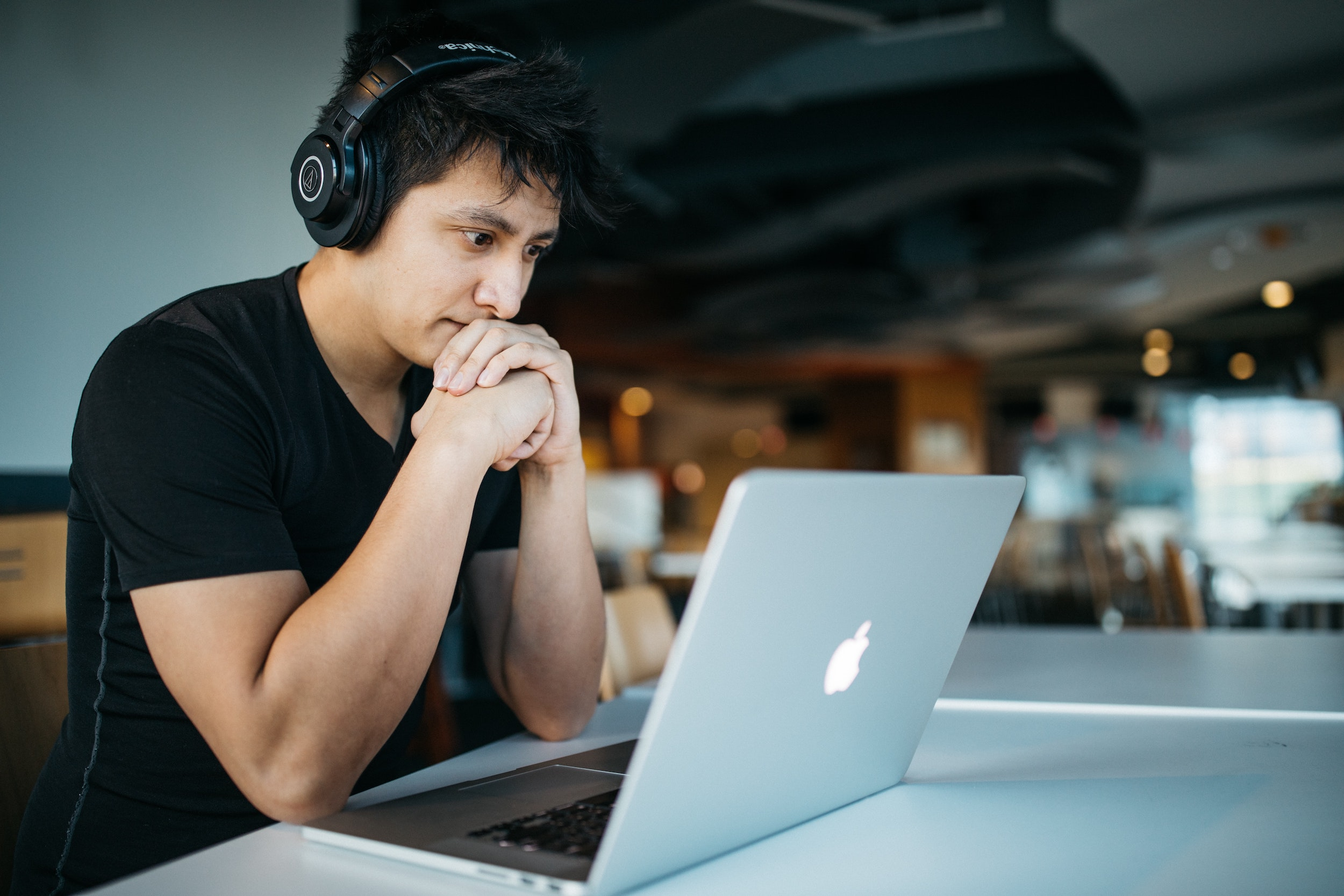 Young male looking at a laptop screen while wearing headphones