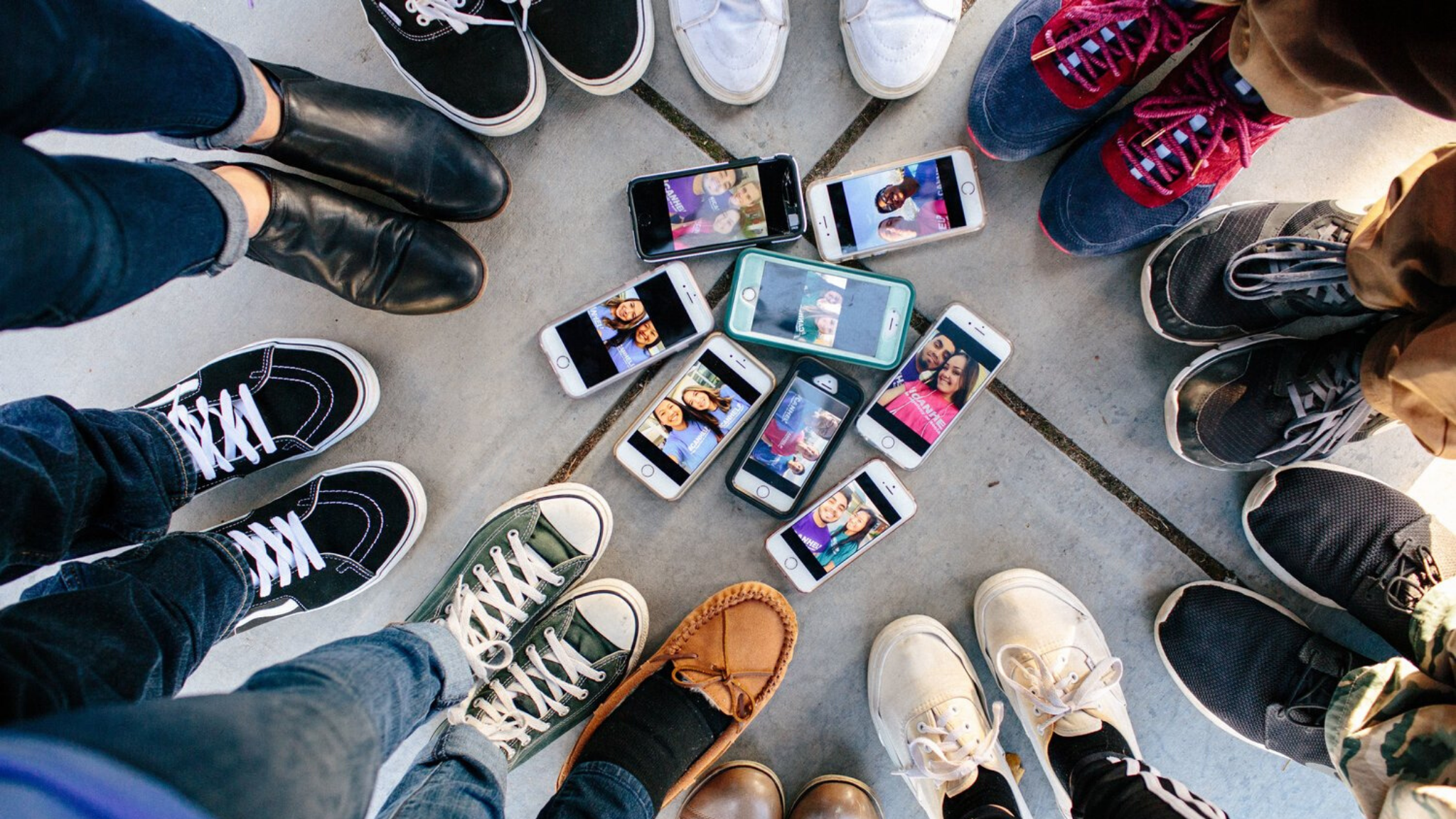 A circle of people's shoes pointing to a group of smartphones.